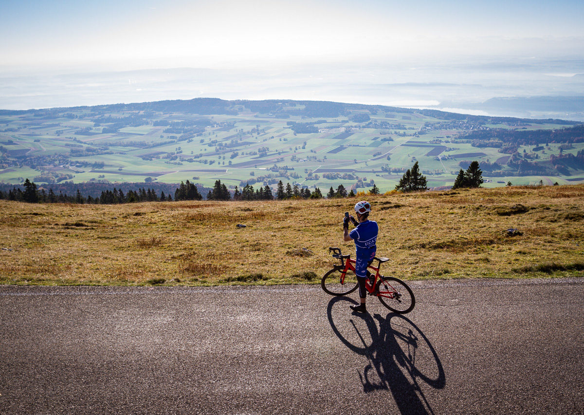 One male cyclist taking a photo of Lake Biel from the climb to Mont Chasseral in Kanton Bern, Switzerland