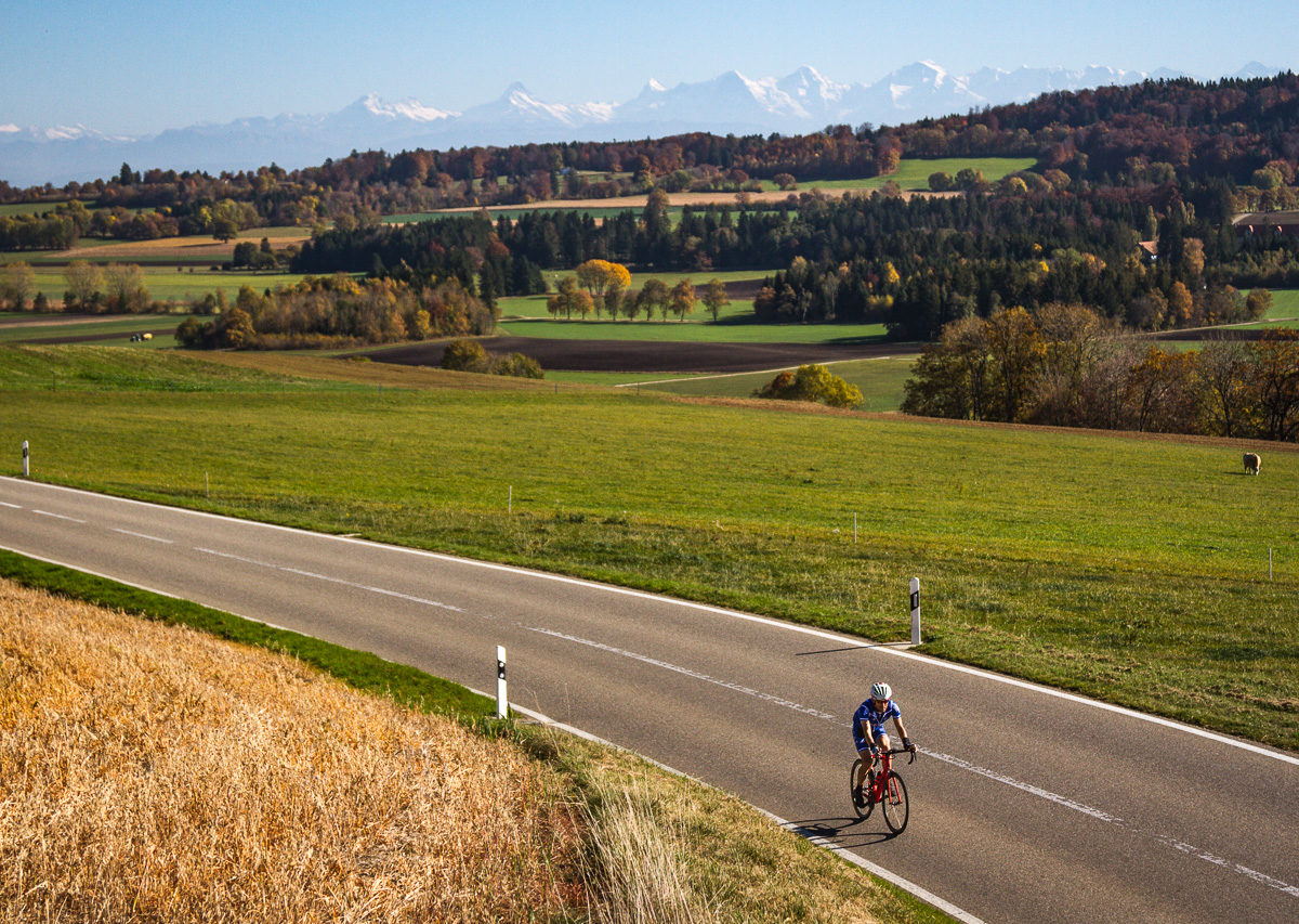 One man riding in the Jura region of Kanton Bern, Switzerland with the Alps in the background