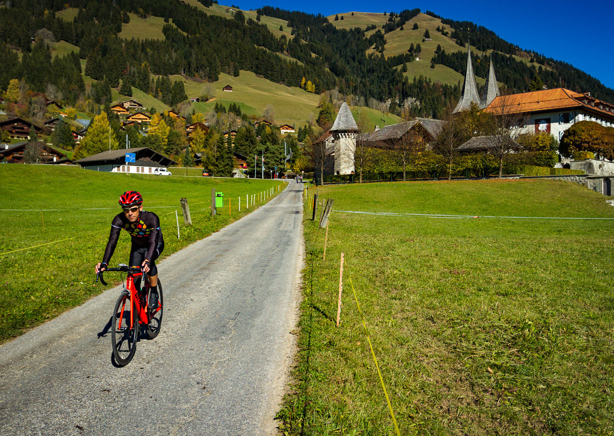 Lone cyclist coming out of Rougemont, Switzerland
