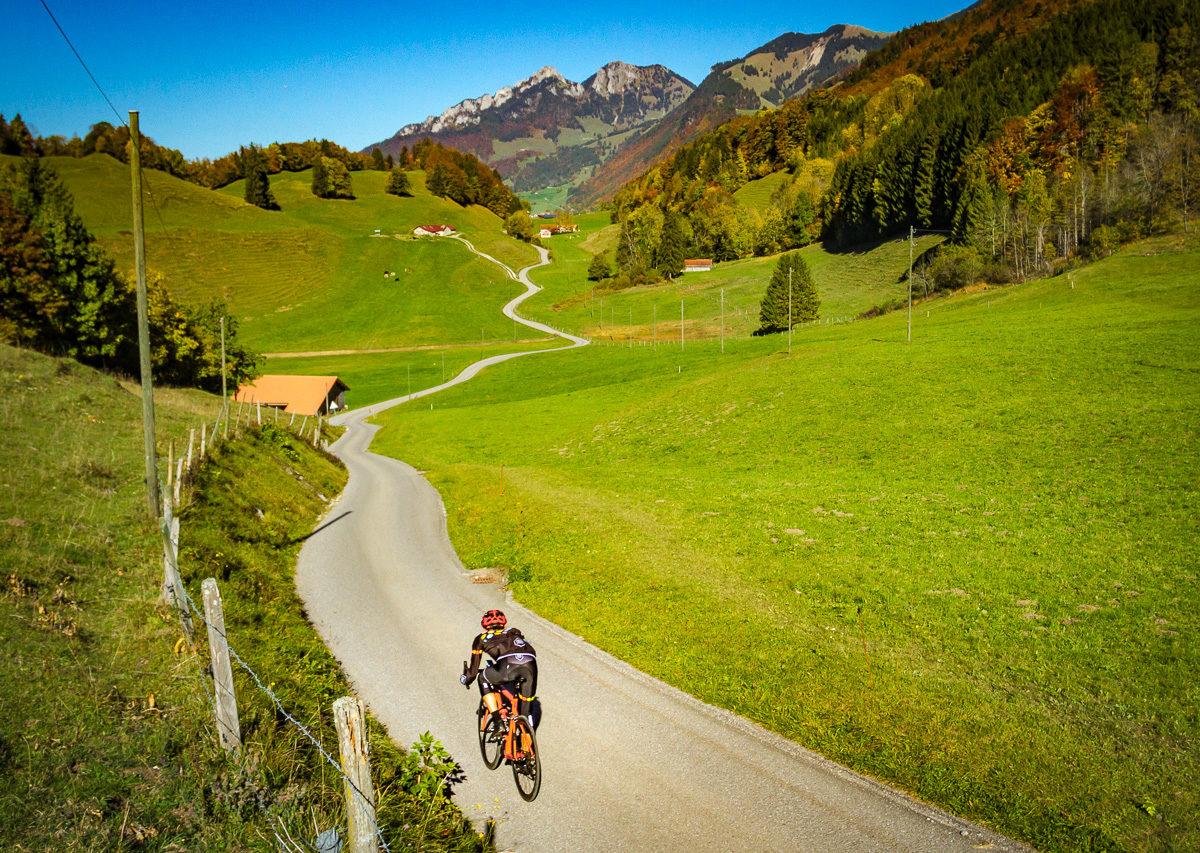 Lone cyclist riding in the Gruyère region in Switzerland