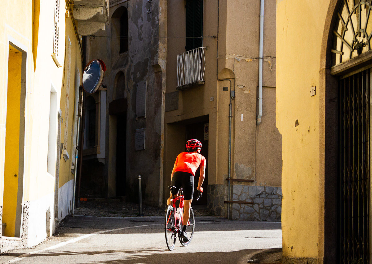 One male cyclist riding in a village along Lago Maggiore in Provincia di Varese, Italy