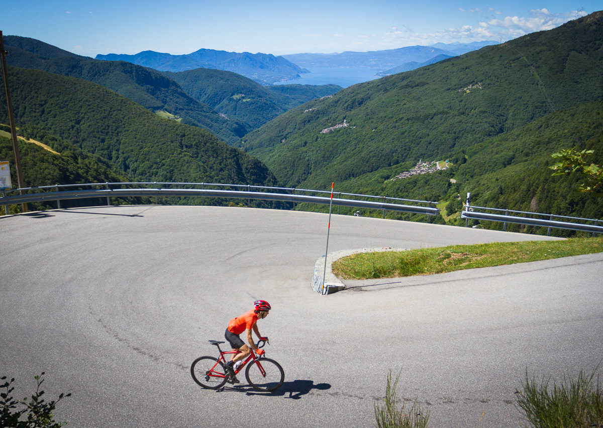 One male cyclist climbing to Alpe di Neggia in Ticino, Switzerland with Lago Maggiroe in the background
