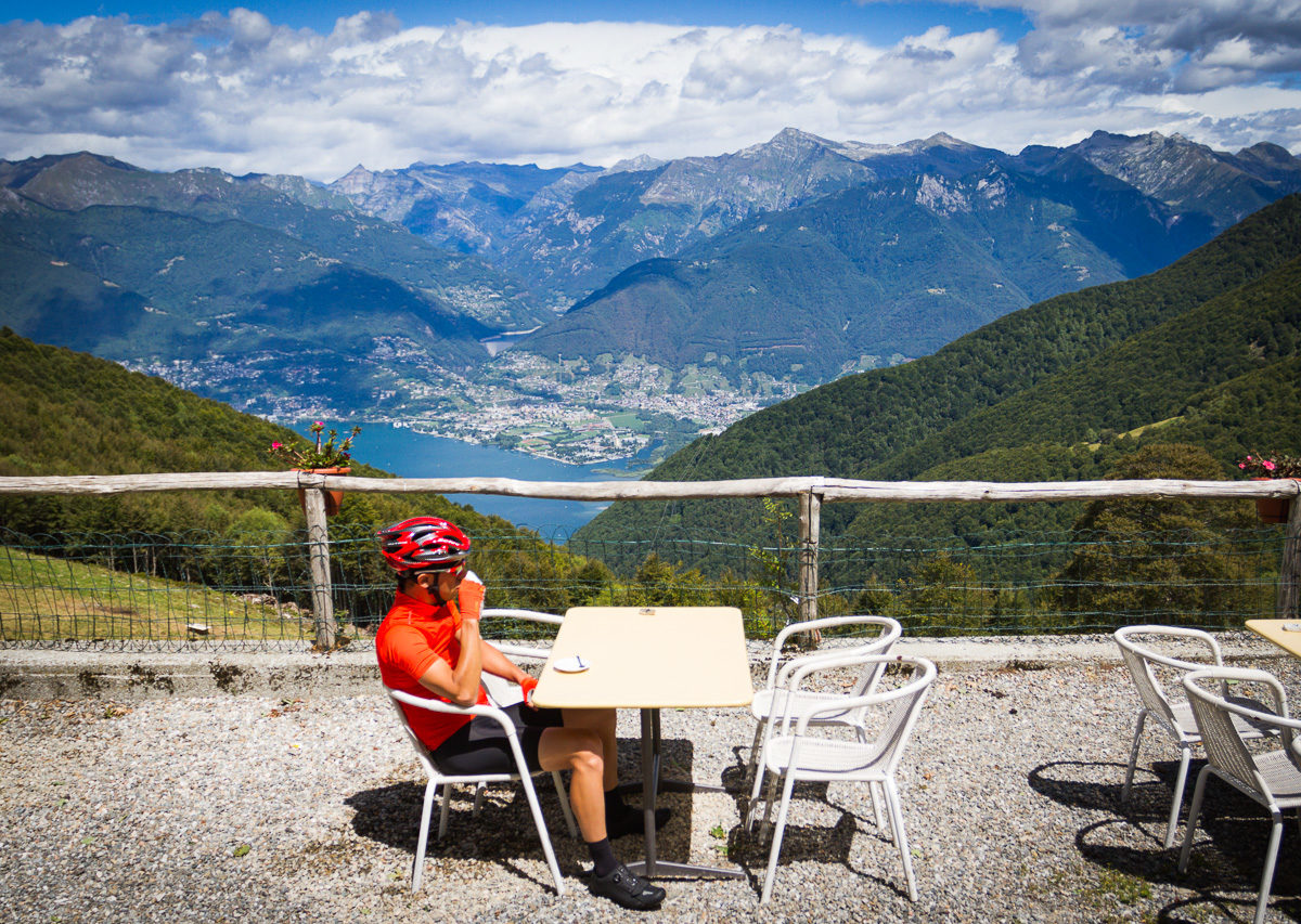 One male cyclist having a coffee at the top of Alpe di Neggia in Ticino, Switzerland with Lago Maggiore and Locarno in the background
