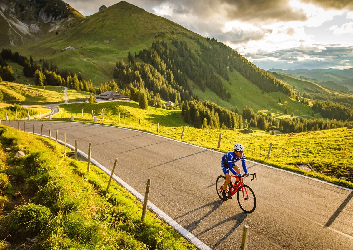 One male cyclist climbing Gurnigelpass at sunset in Kanton Bern, Switzerland